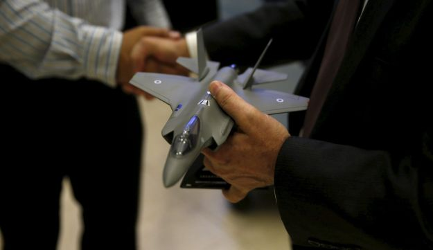 A Lockheed Martin official holds a model of the F-35 during its presentation at the Israeli Air Force house in Herzliya, Israel April 5, 2016.