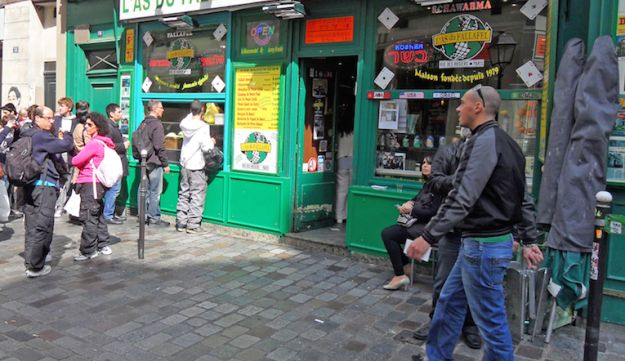 Yomi Peretz, right, approaching a line of tourists waiting to place their orders at The Falafel Ace in the historic Jewish quarter of Paris, April 2012.