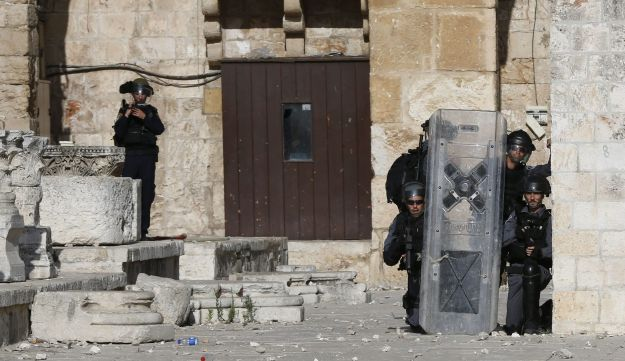 Israeli police take cover as Palestinian protesters throw stones at them at Jerusalem's Al-Aqsa mosque compound during clashes between Israeli police and Muslims for the thrid consecutive day on June 28, 2016 in Jerusalem's Old City.  Israeli authorities announced they were closing Jerusalem's flashpoint Al-Aqsa mosque compound to non-Muslim visitors after a series of clashes between worshippers and police. The decision will apply until the end of the Muslim holy month of Ramadan next week.