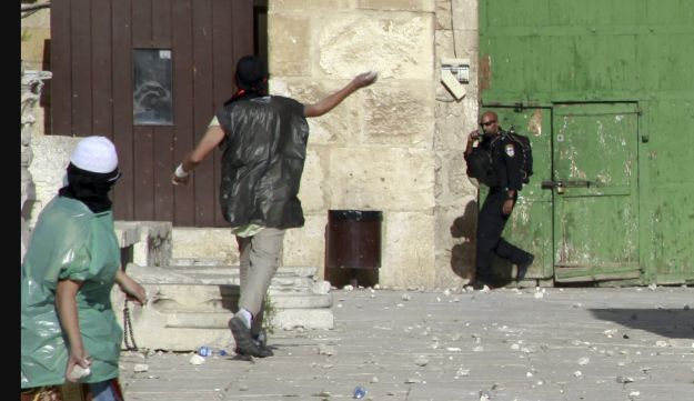 Palestinian youth throw stones at Israeli border police during clashes at al-Aqsa mosque compound in Jerusalem Tuesday, June 28, 2016. Police spokesman said rocks and other objects were hurled toward police forces Jewish worshippers in a nearby plaza. As a result, police decided to close access to Jewish worshippers and other visitors for the remainder of the week to prevent tensions with Muslim worshippers until Ramadan is over.