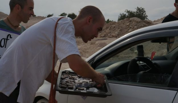 A volunteer from 'Peace of cake' handing out cake to a passerby.
