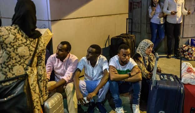 People wait with their luggage outside the Ataturk airport in Istanbul, on June 28, 2016, after two hit the Turkey's biggest airport.