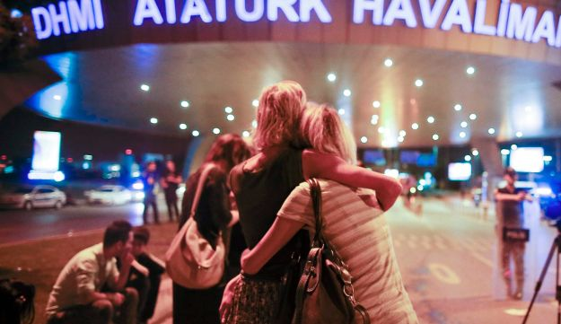 Passengers embrace each other at the entrance to Istanbul's Ataturk airport, early Wednesday, June 29, 2016 following their evacuation after a blast.