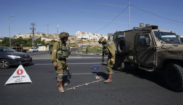 Israeli soldiers set up a checkpoint on the road near the Jewish settlement of Kiryat Arba where a 13-year-old Israeli girl was fatally stabbed in her bedroom on June 30, 2016 in the occupied West Bank outside the Palestinian city of Hebron. A Palestinian attacker broke into the Jewish settlement in the occupied West Bank, fatally stabbing a teenage girl and wounding a security guard before being shot dead, the army said.