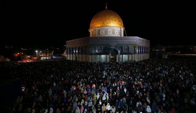 Palestinian Muslim worshippers pray overnight on July 2, 2016 outside the Dome of the Rock in the Al-Aqsa mosques compound in Jerusalem's Old City on the occasion of Laylat al-Qadr.