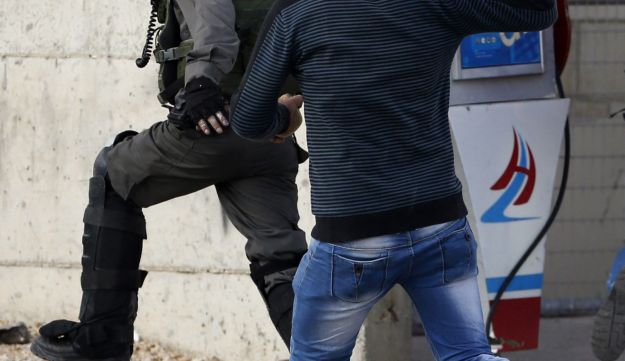 A Palestinian youth holds a stone as he chases a Border Police officer before being run over