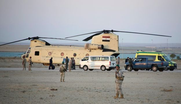 Egyptian soldiers stand guard as rescuers carry bodies of victims of a plane crash