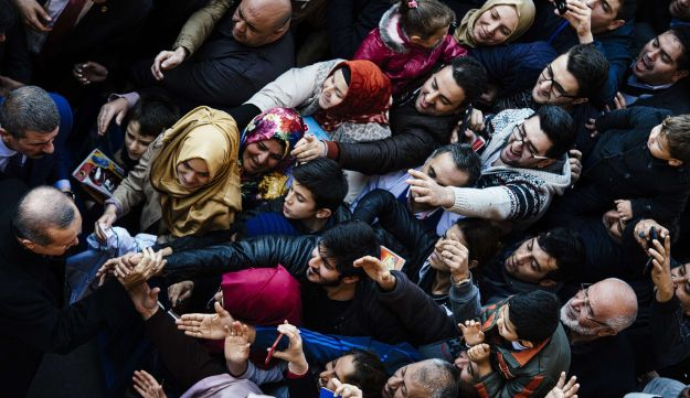 Supporters cheer Turkish President Recep Tayyip Erdogan (left) in front of a polling station in Ista