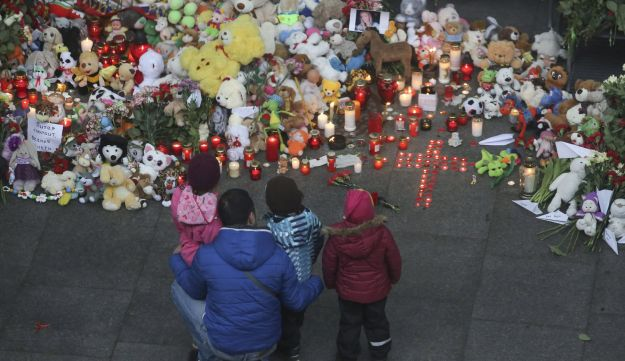 A man and children mourn near a makeshift memorial outside Pulkovo airport in St. Petersburg, Russia