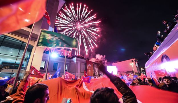 AKP supporters hold a giant Turkish flag as they celebrate after the first results in the country's
