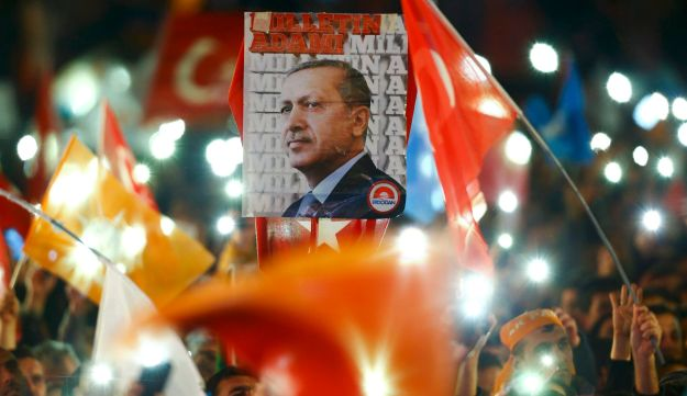 People wave flags and hold a portrait of Turkish President Tayyip Erdogan after AKP take majority in