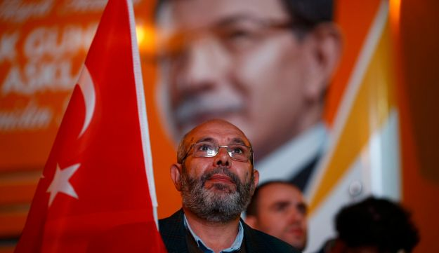 A man holds a Turkish flag as he waits for exit polls outside the AK Party headquarters in Istanbul,
