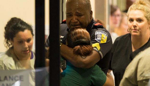 A Dallas Area Rapid Transit police officer receives comfort at the Baylor University Hospital emergency room entrance July 7, 2016, in Dallas, Texas following a shooting that killed five officers.