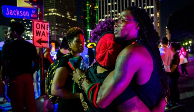 Protestors react after shots were fired during a protest on Thursday, July 7, 2016 in Dallas.  Snipers opened fire on police officers in the heart of Dallas during protests over two recent fatal police shootings of black men.