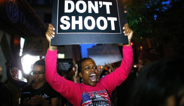A woman holds a banner during a protest in support of the Black lives matter movement in New York on July 9, 2016.