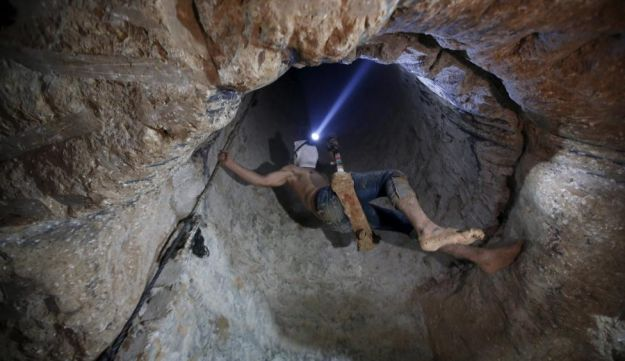A Palestinian worker is lowered into a smuggling tunnel. November 2, 2015.