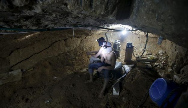 Palestinian workers rest as they repair a smuggling tunnel, November 2, 2015.