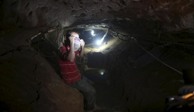 A Palestinian worker sits inside a smuggling tunnel, November 2, 2015.