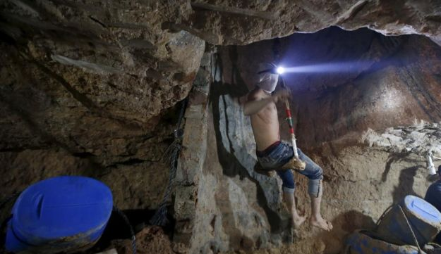 A Palestinian worker is lowered on a rope into a smuggling tunnel, November 2, 2015.