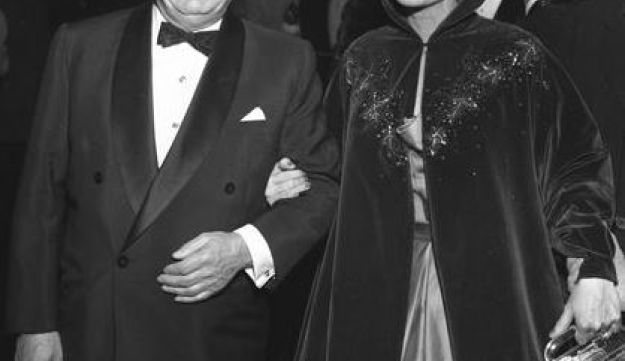 """Actress Joan Crawford on the arm of Louis B Mayer at the """"Torch Song"""" movie premiere in Los Angeles, Calif., 19 November, 1953."""