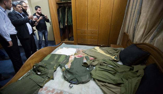 Palestinians take photos of the clothes of late Palestinian President Yasser Arafat in the bedroom of his house, Gaza City, November 11, 2015.