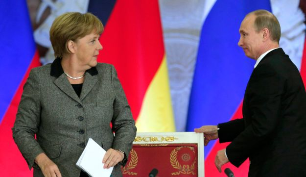 Russian President Vladimir Putin and German Chancellor Angela Merkel look at each other after a signing ceremony during a Russian-German business forum, Moscow, Russia, November 16, 2012.