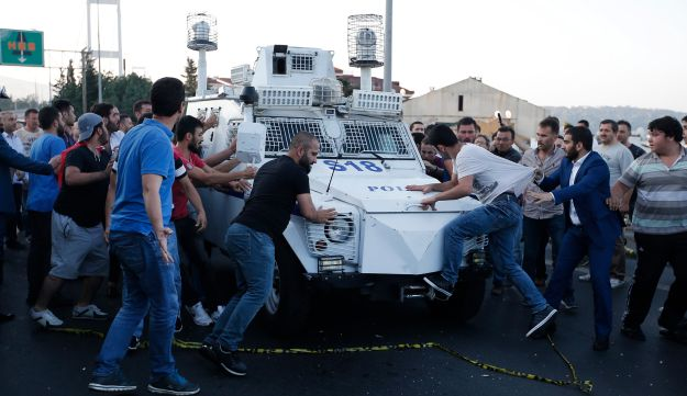 People attack and try to stop a Turkish police armored vehicle, carrying Turkish soldiers that participated in the coup and surrendered, Saturday, July 16, 2016.
