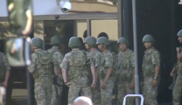 Armed Turkish soldiers waiting at entrance of TRT state television as they prepare to surrender to the police after a failed coup attempt, July 16. 2016.