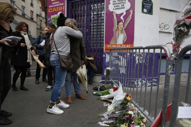 People react as they stand near a rail cordon close to the Bataclan theatre in the 11th district of Paris, on November 14, 2015, the day after a series of attack on the city resulting in the deaths of more than 128 individuals. Some 80 people were gunned down at the Bataclan theatre in Paris late November 13, during a concert by the US band Eagles of Death Metal.
