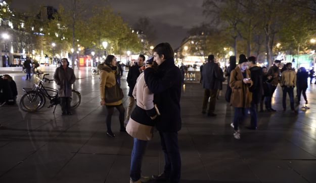 A couple embraces as they pay tribute to the victims of the attacks in and around Paris, at the Place de la Republique square in Paris, on November 14, 2015.