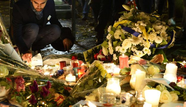 A man lights candles at a makeshift memorial next to the Bataclan concert hall on November 16, 2015 in Paris. Islamic State jihadists claimed a series of coordinated attacks by gunmen and suicide bombers in Paris that killed at least 129 people in scenes of carnage at a concert hall, restaurants and the national stadium.