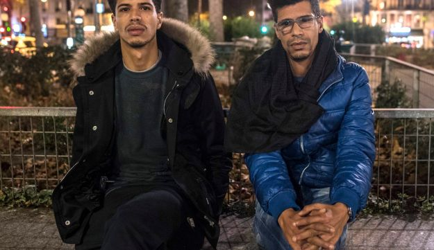In this photo taken on Sunday, Nov. 15, 2015, Khaled Saadi, 27, left and Abdullah Saadi, 38, listen during an interview with the Associated Press. Khaled Saadi was working in La Belle Equipe restaurant, where his sister was celebrating her birthday, when the attackers assaulted the cafe. 35-year-old Halima died on the spot. 36-year-old Hodda was severely wounded and barely breathing, and Saadi did everything he could to try to save her. In vain.