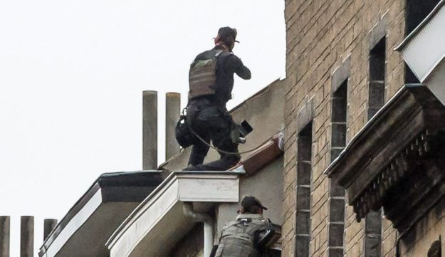 Special intervention forces climb to the top of a roof, preparing to enter a house in Brussels on November 16, 2015.