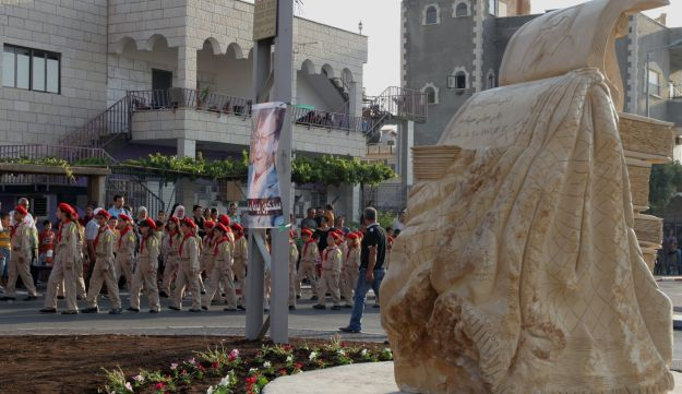 Memorial Day for Mahmoud Darwish, Jedida. Schoolchildren in light khaki uniforms, wearing red ties and berets, march past a stone memorial to the poet.
