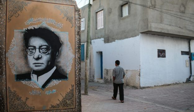 A man walks past street art showing the late Palestinian poet Mahmoud Darwish, in Erriadh, south of Tunis, Tunisia, October 28, 2015.