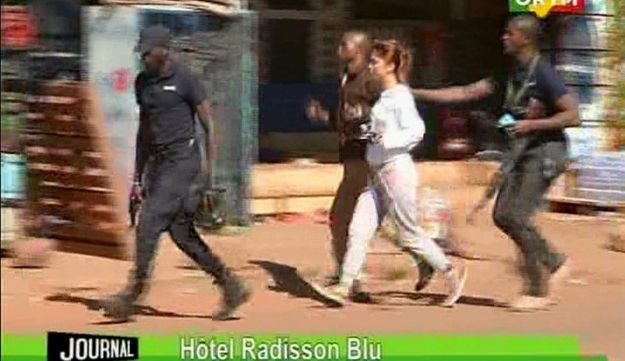 TV image taken from Mali TV ORTM, a woman is led away by security personnel from the Radisson Blu Hotel hotel in Bamako, Mali, Friday Nov. 20, 2015