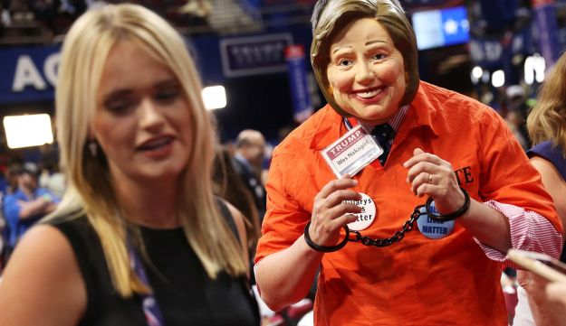 An attendee dresses as US Democratic presidential candidate Hillary Clinton with handcuffs prior to the start on the fourth day of the Republican National Convention on July 21, 2016
