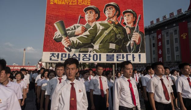 A propaganda poster is displayed during a rally in support of North Korea's stance against the US, on Kim Il-Sung square in Pyongyang on August 9, 2017.