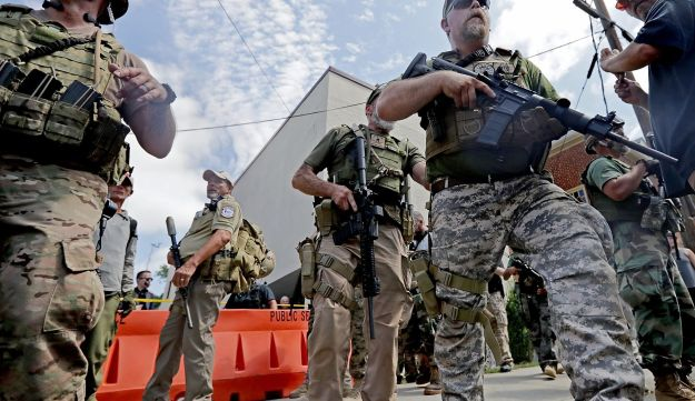 White nationalists wearing body armor and holding combat weapons evacuate comrades who were pepper sprayed by Virginia State Police after the protest turned violent, Charlottesville, August 12, 2017.