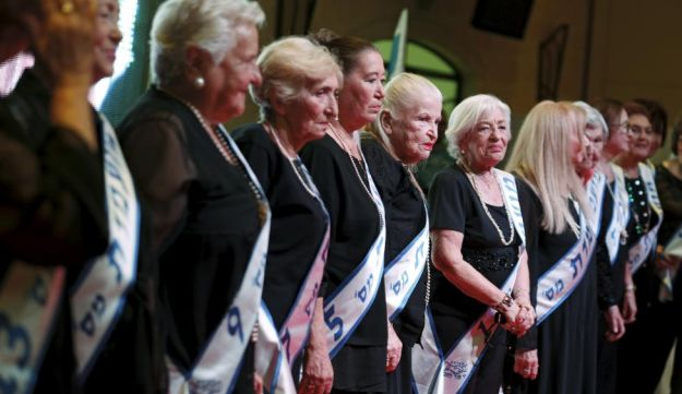 Holocaust survivors stand on a stage during a beauty contest for survivors of the Nazi genocide in the northern Israeli city of Haifa. November 24, 2015.