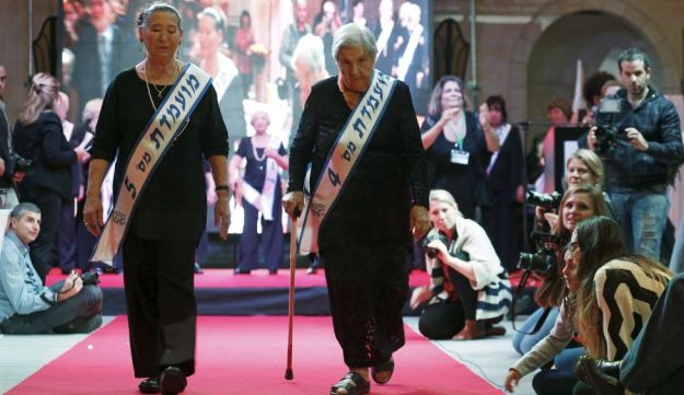Judith Rosenzweig, 81, (R) and Rivka Shtanger, 74, (L) both Holocaust survivors, walk on a runway during a beauty contest for survivors of the Nazi genocide in the northern Israeli city of Haifa. November 24, 2015.