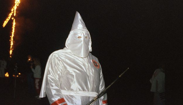 A member of the Knights of the Ku Klux Klan stands by a burning cross near Zinc, Ark., Oct. 12, 1991.