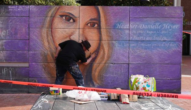 An artist works on a mural of Heather Heyer prior to a memorial service for her in Charlottesville, Virginia, U.S., August 16. 2017.