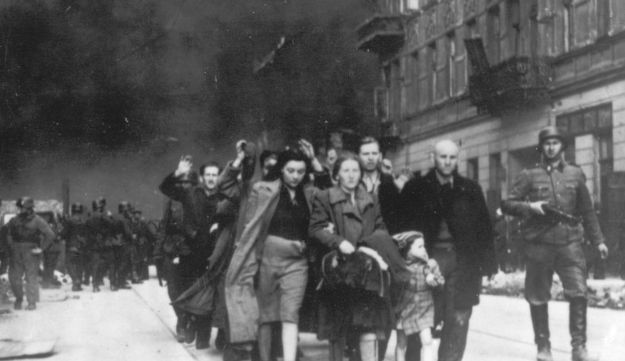 A group of Polish Jews being led away for deportation by German SS soldiers during the destruction of the Warsaw Ghetto by German troops in 1943.