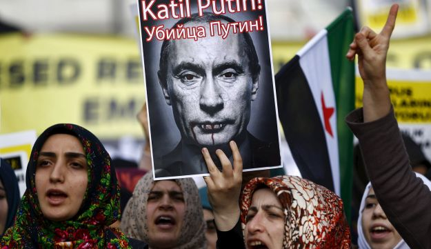 Pro-Islamist demonstrators hold a defaced poster of Vladimir Putin during an anti-Russian protest in Istanbul, Turkey, November 27, 2015.