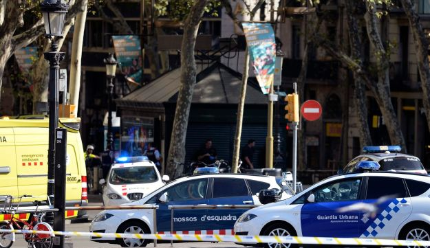 Policemen stand next to vehicles in a cordoned-off area after a van plowed into the crowd in Barcelona, August 17, 2017.