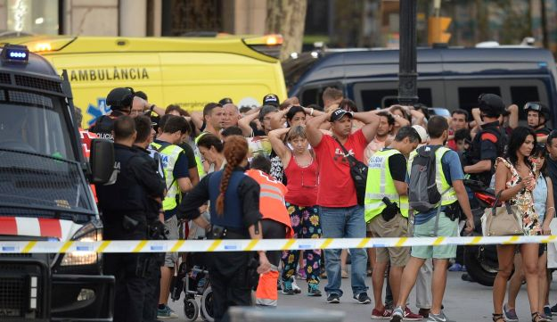 Police officers check the identity of people after a van plowed into the crowd in central Barcelona, August 17, 2017.