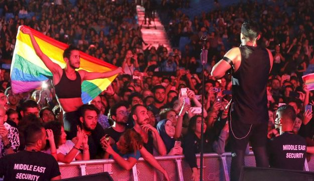 A fan of Lebanese alternative rock band Mashrou' Leila holds a rainbow flag during their concert at the Ehdeniyat International Festival in Ehden town, Lebanon August 12, 2017