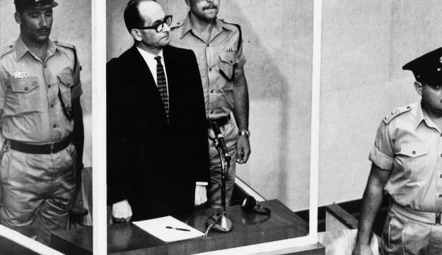 A 1962 file photo shows Adolf Eichmann standing in his glass cage, flanked by guards, in the Jerusalem courtroom where he was tried for war crimes committed during World War II.