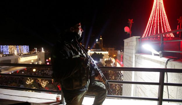 A member of Palestinian National Security Forces stands guard during a Christmas tree lighting ceremony outside the Church of the Nativity in the West Bank town of Bethlehem December 3, 2016.
